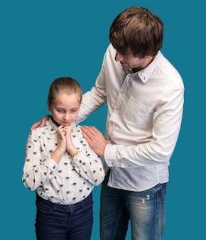 Chica de aspecto triste con el padre en una pared azul