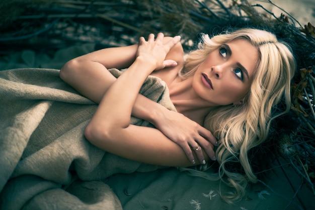 Chica asustada acostada cerca de las ramas de los árboles con los brazos cruzados y mirando a otro lado, cubierta con una manta beige