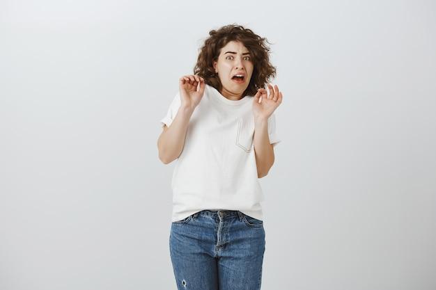 Chica asustada y disgustada levantando las manos haciendo muecas de aversión y disgusto