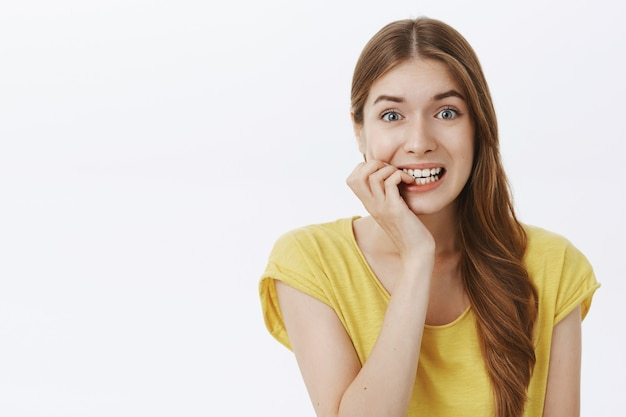 Chica asustada insegura mirando nerviosa y mordiendo las uñas