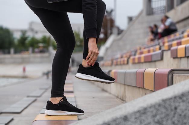 Chica atar cordones de zapatos en zapatillas de deporte