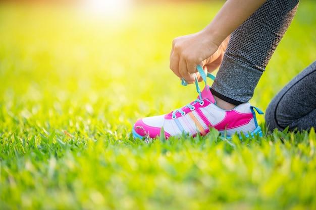 Chica atar zapatos para correr