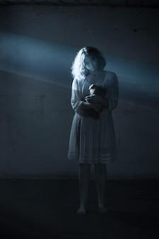 Chica aterradora con vestido blanco de la película de terror en la habitación