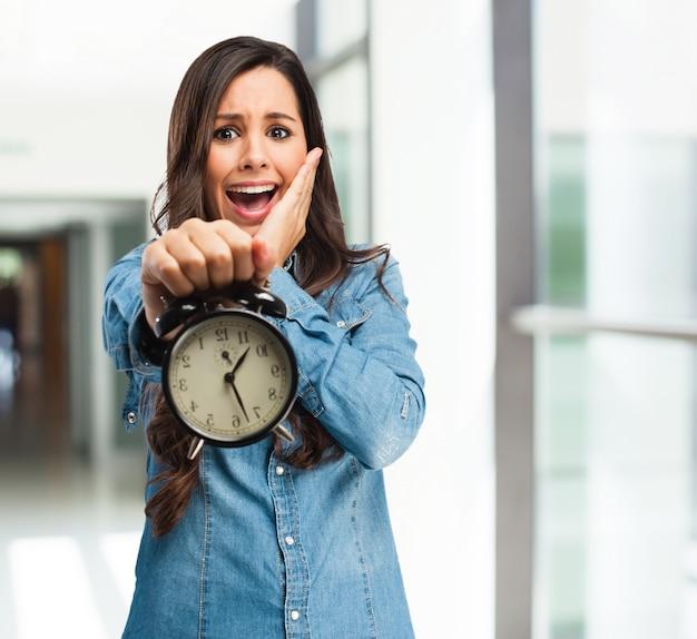 Chica aterrorizada sujetando un reloj