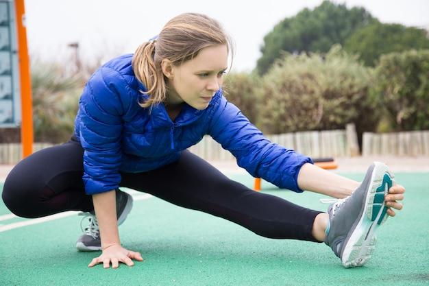 Chica atleta enfocada calentando afuera