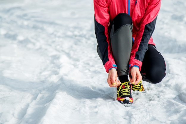 Chica atleta tratando de correr zapatillas preparándose para correr