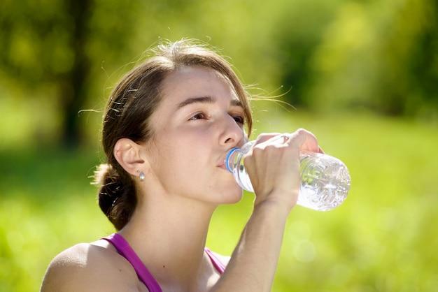 Chica atlética agua potable después del ejercicio