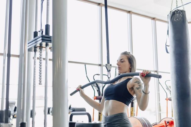 Chica atlética atractiva entrena hombros en simulador. vista de los músculos de la espalda. estilo de vida saludable.