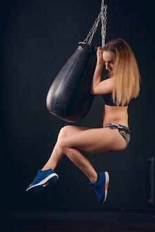 Chica atlética colgando proyectil deportivo en pose sexy