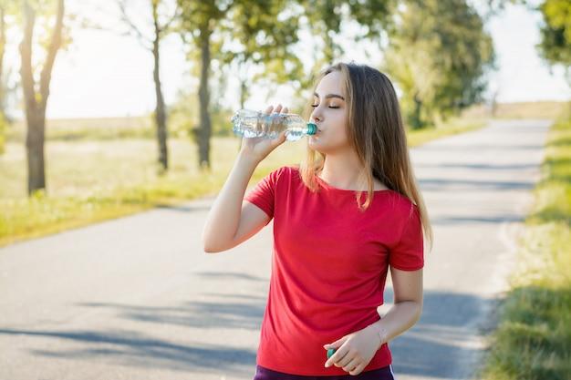Chica atlética en pantalones cortos violetas y camiseta roja bebiendo agua de una botella de plástico después de hacer ejercicio en la mañana.