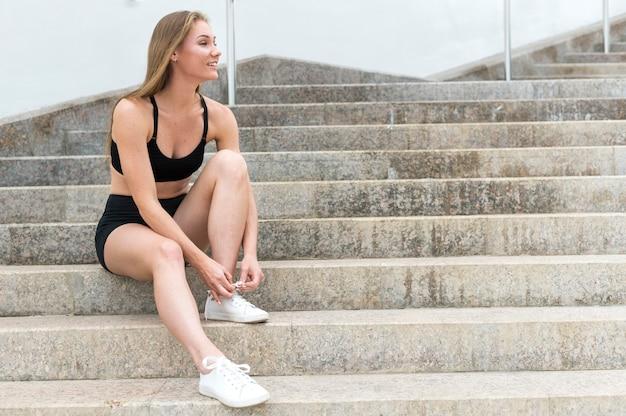 Chica atlética de pie en las escaleras y atar cordones de los zapatos