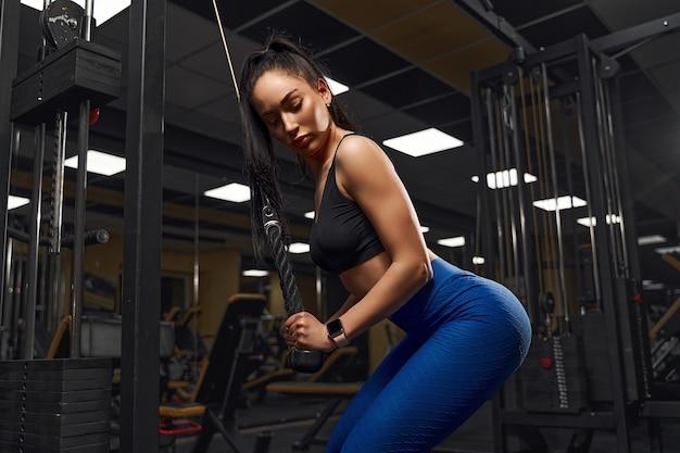 Chica atlética sexy ejercitándose en el gimnasio