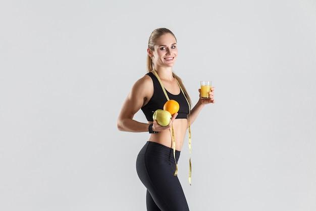 Chica atlética sosteniendo frutas y jugos y sonriendo con dientes