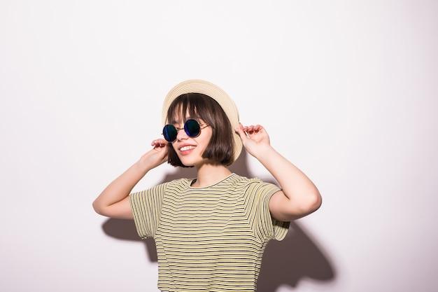 Chica atractiva adolescente hipster con sombrero, gafas de sol aislado