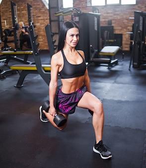 Chica atractiva alegre haciendo ejercicio se lanza con pesas en sus manos en el gimnasio