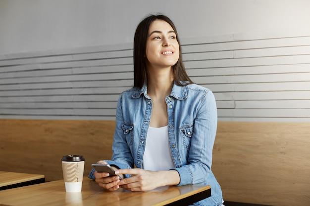Chica atractiva alegre con el pelo oscuro sentada en la cafetería, bebe café y conversa con un amigo en el teléfono inteligente y luego gira la cabeza para ver al novio a través de la ventana.