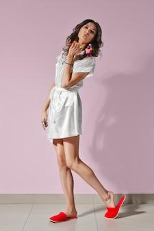 Chica atractiva en bata de baño y zapatillas caminando y dando beso de aire. estilo de playa de verano.