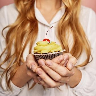 Chica atractiva con una camisa blanca está sosteniendo cupcakes