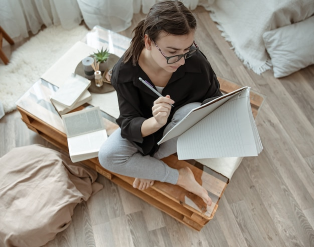 Chica atractiva en casa sentado con un cuaderno y un bolígrafo entre libros vista superior.