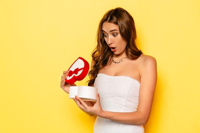 Chica atractiva con caja de regalo de apertura de cara sorprendida, con la boca abierta de par en par
