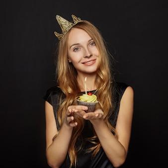 Chica atractiva con una corona y cupcake