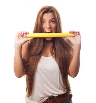 Chica atractiva crujido lápiz grande.