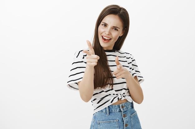 Chica atractiva descarada y emocionada señalando con el dedo, felicitaciones, gesto de felicitaciones, alabando a la persona