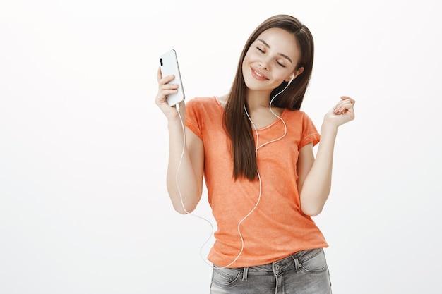 Chica atractiva despreocupada bailando con los ojos cerrados, escuchando música en el teléfono móvil en auriculares