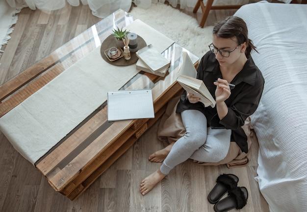 Chica atractiva con gafas lee un libro sentado en un puf en casa.