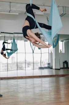 Chica atractiva en el gimnasio durante yoga y fly yoga, posando y luciendo bien