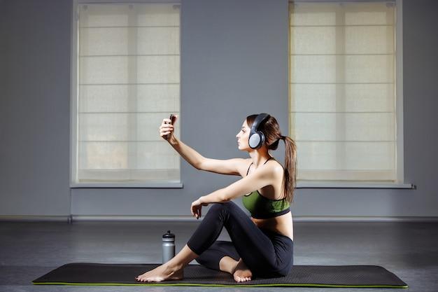Chica atractiva haciendo un selfie después de hacer ejercicio en el gimnasio.