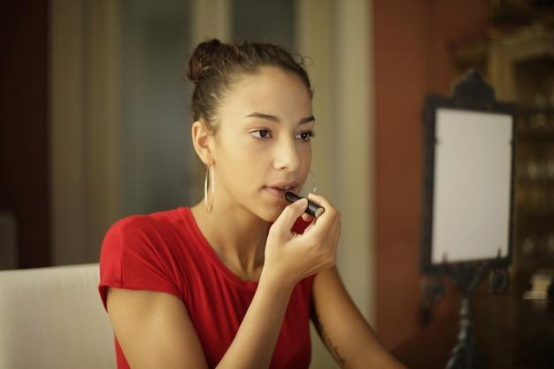 Chica atractiva joven arreglando su maquillaje frente al espejo en la habitación