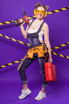 Chica atractiva joven constructor en mono de mezclilla y gafas de pie con destornillador y caja de herramientas