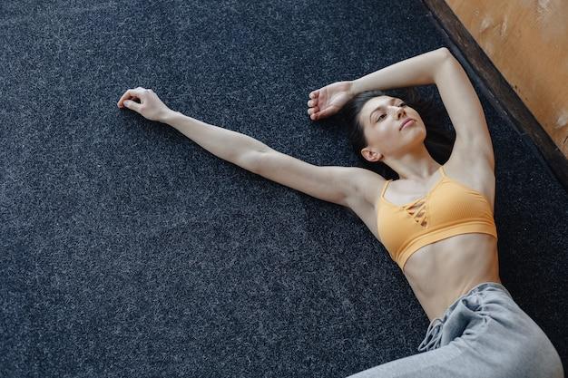 Chica atractiva joven fitness acostado en el piso cerca de la ventana descansando en clases de yoga