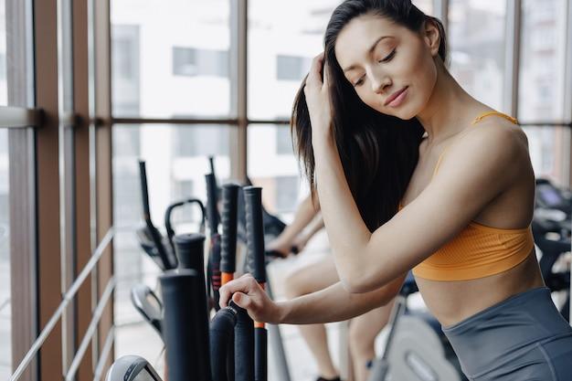 Chica atractiva joven en el gimnasio en bicicleta de ejercicio, fitness y yoga