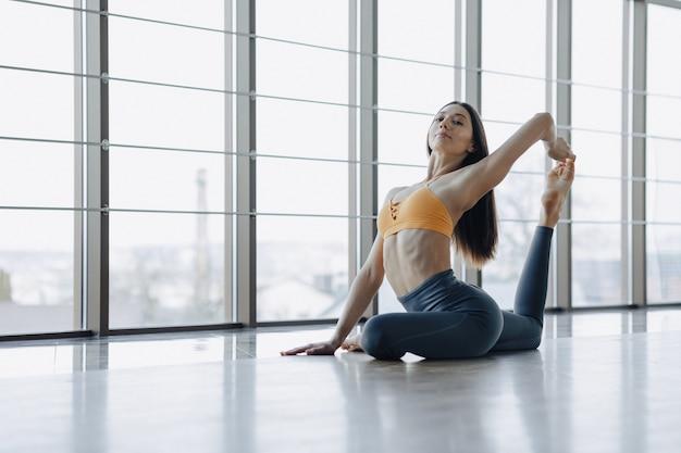 Chica atractiva joven haciendo ejercicios de fitness con yoga en el piso de ventanas panorámicas