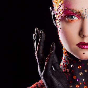 Chica atractiva joven en maquillaje artístico brillante, pintura corporal. media cara