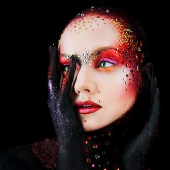 Chica atractiva joven en maquillaje artístico brillante, pintura corporal. perfil