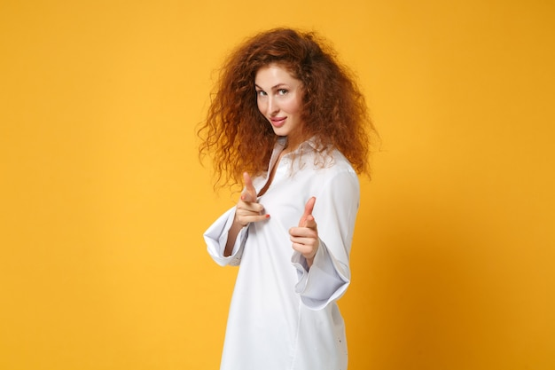 Chica atractiva joven pelirroja en camisa blanca casual posando aislada en la pared naranja amarilla