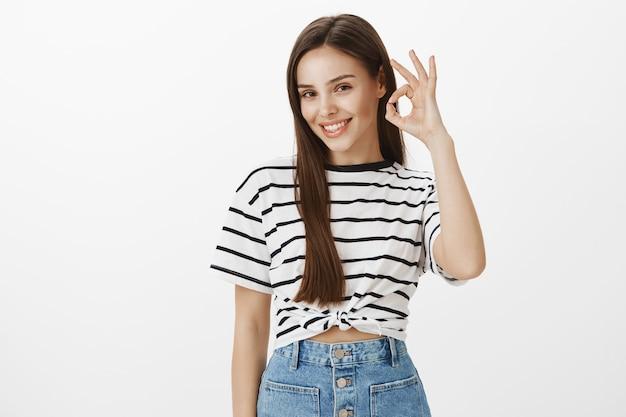 Chica atractiva joven segura que sonríe y garantiza la calidad, recomienda el producto, felicita la elección perfecta