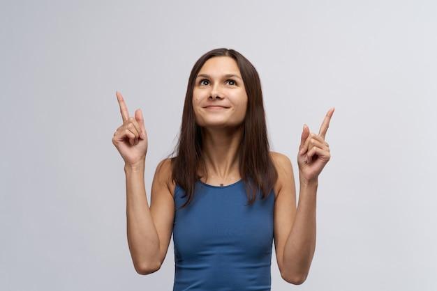 Chica atractiva joven sonriente en camiseta azul apretada y con el pelo largo y liso oscuro mira hacia arriba y el dedo índice apuntando hacia arriba. el concepto de espacio publicitario y la dirección de la vista.