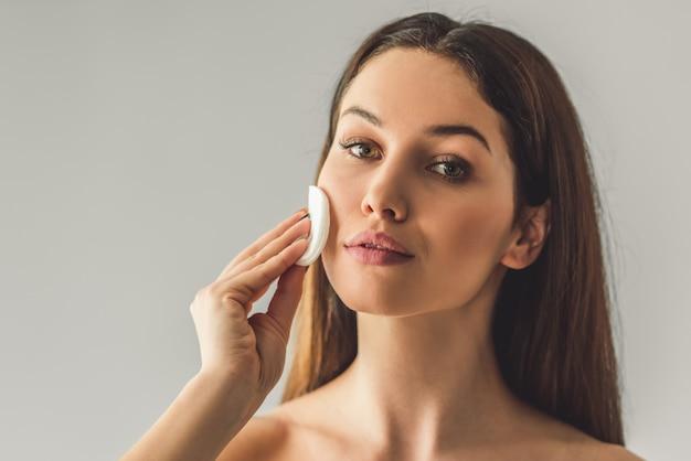 Chica atractiva se limpia la cara con un algodón