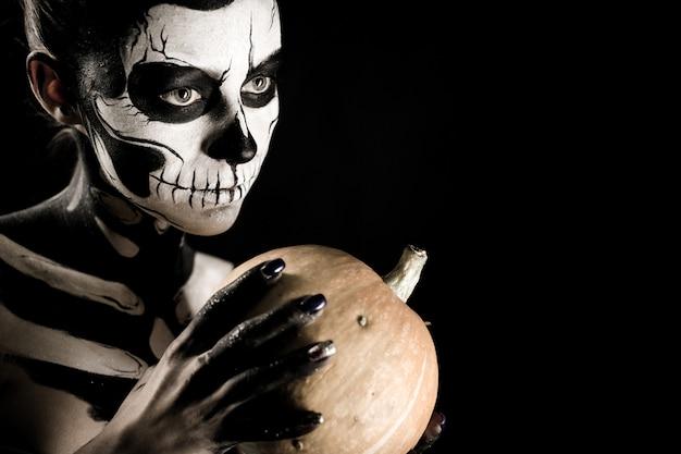 Chica atractiva con maquillaje esqueleto sostiene una calabaza