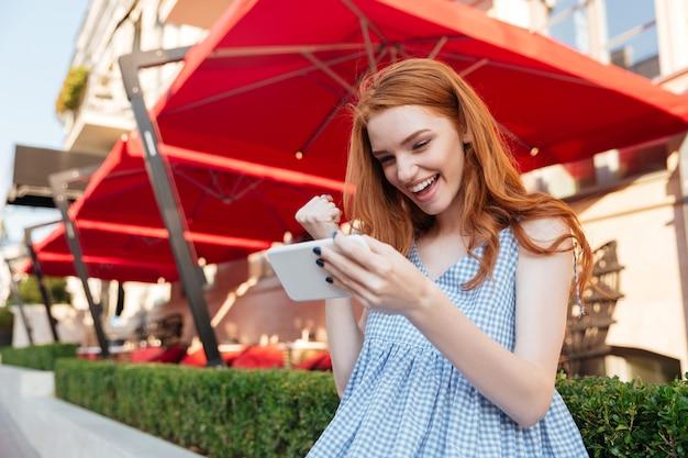 Chica atractiva pelirroja jugando en el teléfono móvil