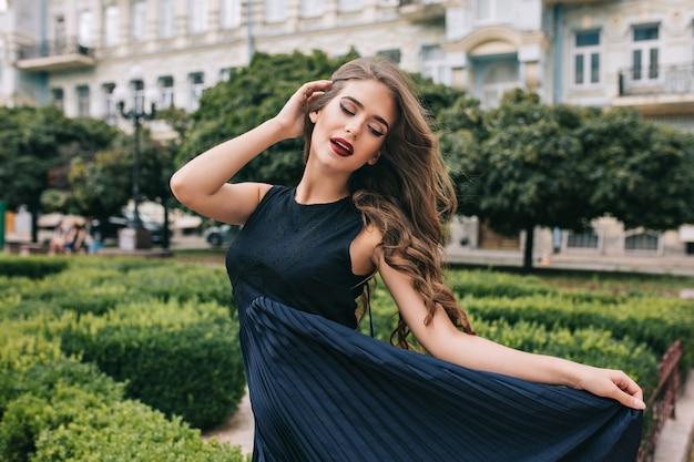 Chica atractiva con pelo largo y rizado posando en la ciudad