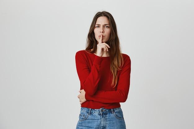 Chica atractiva pidiendo guardar secreto, callar con el dedo presionado sobre los labios, por favor, cállate