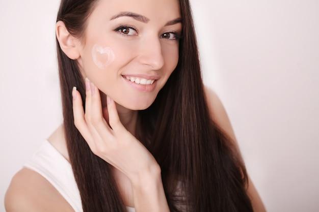 Chica atractiva poner crema antienvejecimiento en su cara