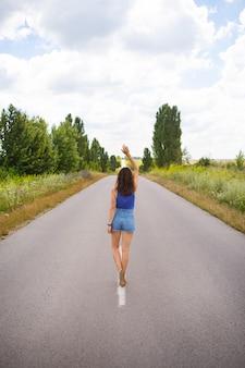 Chica atractiva, posa de pie, manos arriba en medio de una carretera asfaltada cerca del campo, copia espacio para contenido.