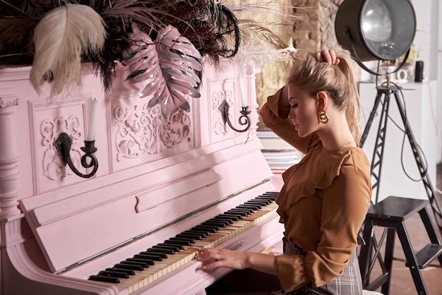 Chica atractiva quedarse en casa en autoaislamiento y tocar el piano. aficiones: ¿qué hacer en casa?