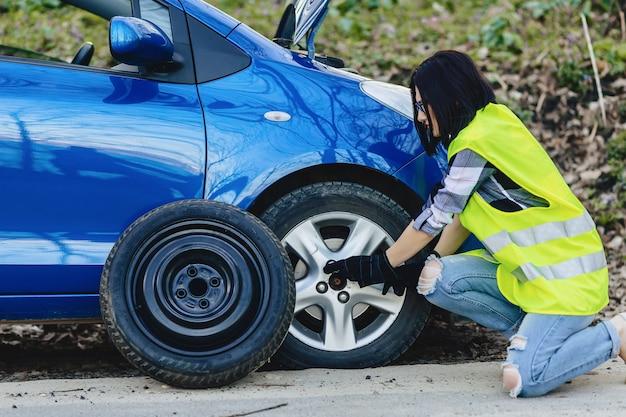 Chica atractiva quitar la rueda del coche en la carretera solo